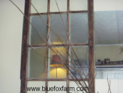 Old window placed over a mirror gives a rustic ambiance