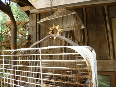 Wiggly twig handle embellishes this great bird cage...