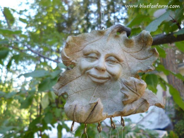 The Green Man is a common motif in garden art, this one is a wind chime...