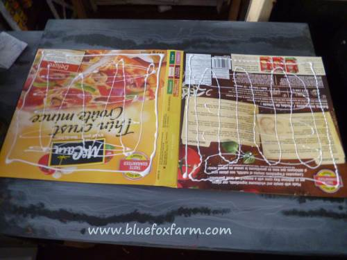 White glue is applied to the shiny side of the frozen pizza box...