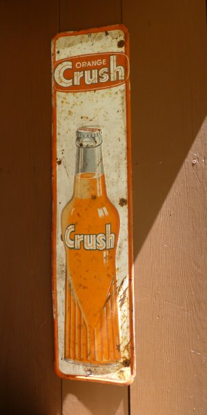 A rustic example of the common Orange Crush tin sign