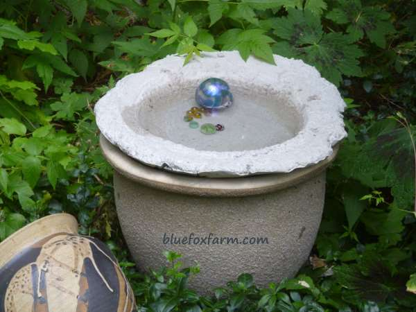 Soil  cement bird bath in place, complete with marbles for decoration