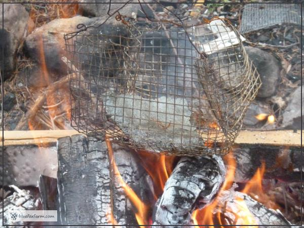 Broken piece of hypertufa pot in a metal basket over the flame
