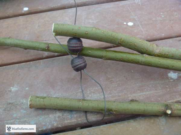 Three twigs for legs, with beads in between