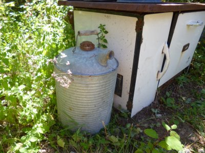 Zinc gasoline can beside the (thankfully!) non-working vintage wood stove